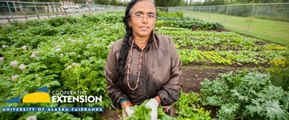 Photograph of woman standing in field with UAF Cooperative Extension logo
