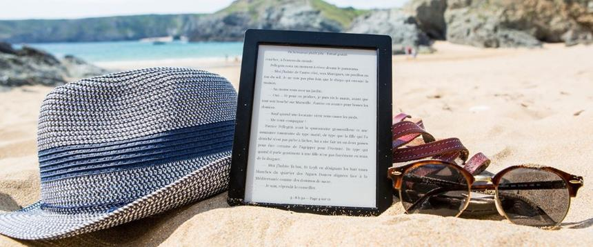 Photograph of eReader tablet on sandy beach with hat and sunglasses