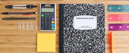 Photo of pencils, paperclips, calculator, composition book and rulers