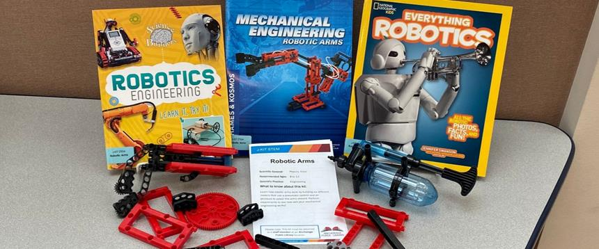 Photo of books and plastic gear pieces included in robotic STEM Kit