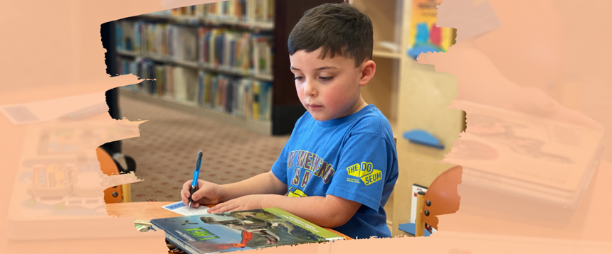 Boy sitting at library table looking at book and writing on Kids Pick bookmark