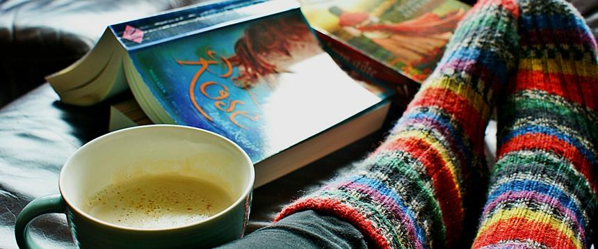 Photo of feet up on couch in colorful socks next to book and cup of coffee.
