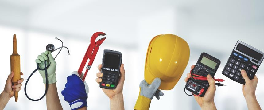 Photo of hands holding up a rolling pin, stethoscope, wrench, card reader, construction hat, electricity monitor and calculator